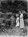 View of a woman, and a girl, standing next to bushes and trees (AM 80584-1).jpg