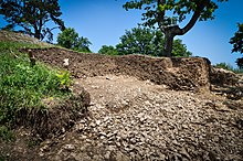 Photographie en couleurs d'une large tranchée creusée dans un terrain en pente, des gravats et des écofacts blancs parsemant le fond de l'excavation.