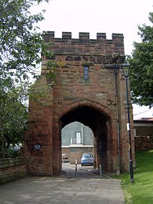A crenellated tower with a large arched gateway