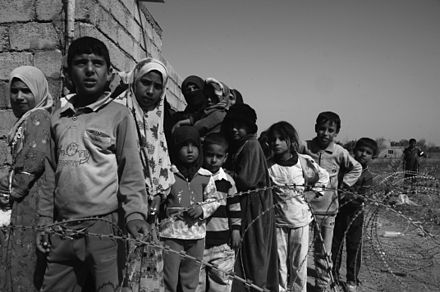 Local citizens from the Jana bi Village wait their turn to gather goods from the Sons of Iraq (Abna al-Iraq) in a military operation conducted in Yusufiyah, Iraq. Waiting for goods.JPG