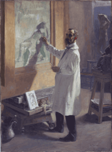 A man wearing a white smock working on a painting