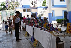 Woman looking at Alebrijes for sale at the weekly market