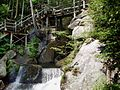 Wooden bridge in the forest over water and rocks.jpg