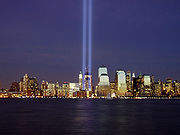 Looking across the Hudson river at night toward the lower Manhattan skyline, two motionless shafts of light point straight up into the sky from ground zero