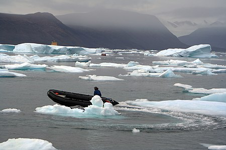 Zodiacs navigate between icebergs in Arctic