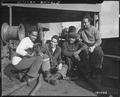"""Members of a `CHECKERBOARD' crew that brought a Liberty Ship from the U.S. to England, fondle their mascot `BOOKER.' (L - NARA - 531167.tif"