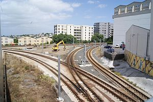 Auckland railway electrification - The same junction as above in December 2010, with some of the traction poles in place. Newmarket Station is just around the corner of the building at right, with the tracks to Britomart going to left of picture. The tracks in the foreground are those of the Western Line.