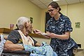 A Sailor feeds a patient at St. Dominic's Senior Care Center. (16927319772).jpg