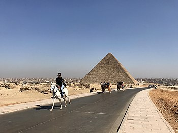 A horse and rider touring the pyramids of Giza, in Cairo Egypt.jpg