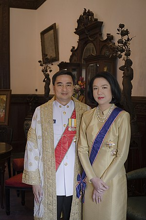 Abhisit Vejjajiva - Abhisit Vejjajiva, wearing prime ministerial attire, including the golden brocaded ''Senamat'' gown (ครุยเสนามาตย์), and his wife, Dr Pimpen, wearing a Thai silk dress