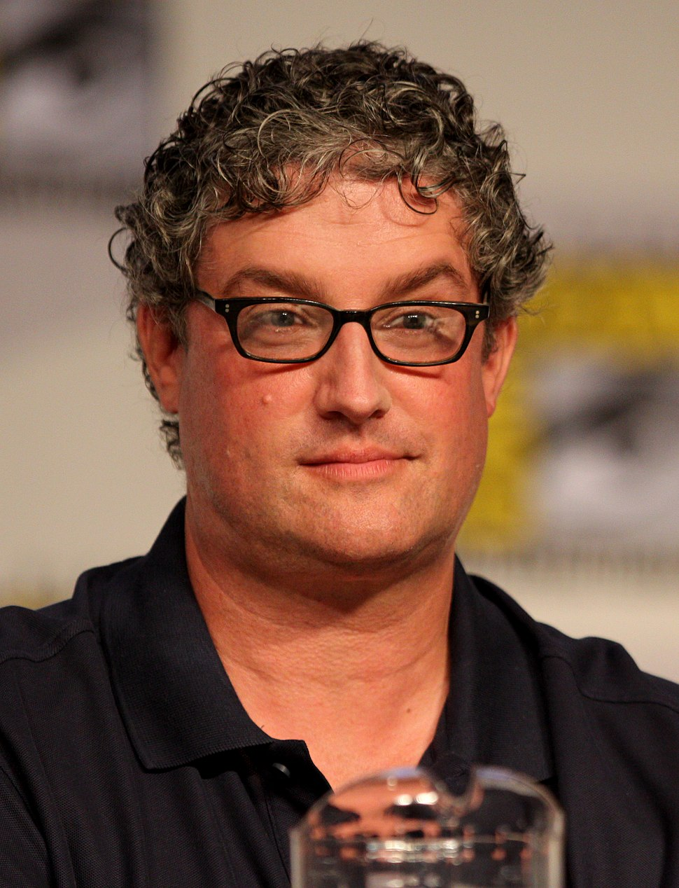 A man with glasses and a black shirt sits in front of a microphone.