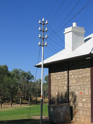 Unbalanced line - Telegraph lines on an Oppenheimer pole outside the historic Alice Springs telegraph station on the now disused Australian Overland Telegraph Line