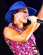 Woman wearing a black gown and sining in to a microphone.