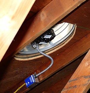 Attic fan - An attic fan installed underneath a roof.