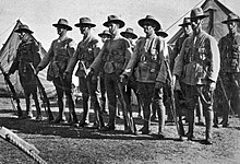 Men in military uniforms with rifles and bandoliers stand at ease in ranks