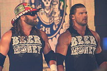 "Two adult white males wearing black shirts with ""Beer Money"" in green text on the front. Both have long black hair, one wearing a cowboy hat."