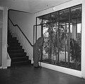 Bejaarde man met wandelstok staat bij een plantenbak in een trappenhuis, Bestanddeelnr 252-9119.jpg