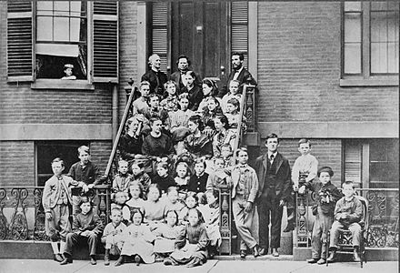 "Bell, top right, providing pedagogical instruction to teachers at the Boston School for Deaf Mutes, 1871. Throughout his life, he referred to himself as ""a teacher of the deaf"". Bell at the Pemberton Avenue School for the Deaf, Boston, from the Library of Congress. 00837v.jpg"