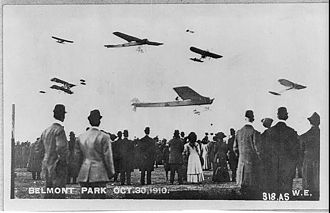 """Aero Club of America - Photo composite of the 1910 event sponsored by the Aero Club of America """"Crowd watching seven planes in air at Belmont Park air show, New York""""."""