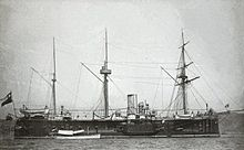 A three-masted black and white ship at port.