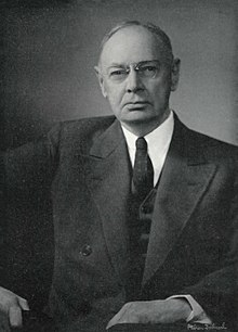 Formal black and white portrait of an older man, wearing glasses, in a suit