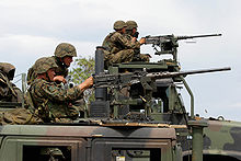 In the foreground, a HMMWV, with a MTVR in the background. Both vehicles have M2 machine guns mounted and U.S. Marines firing them.