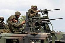 En la malfono, HMMwV, kun MTVR en la fono. Ambaŭ veturiloj havas M2 mitralojn muntitaj kaj usonaj marsoldatoj pafantaj ilin.