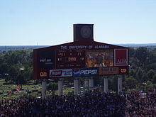 Large scoreboard in an American football stadium surrounded by crowded stands.