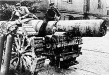 Tre menn sitter på toppen av et stort artilleristykke.