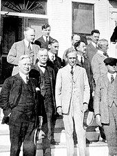 A black and white photograph of about ten white men in three-piece suits standing on the steps of a building with columns