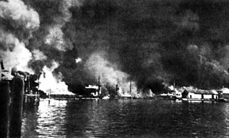 Philippine Navy - Sangley Point Cavite Navy Yard burning after a Japanese air attack on 10 December 1941. Small-arms shells explode (left) and a torpedo-loaded barge (center) burns.