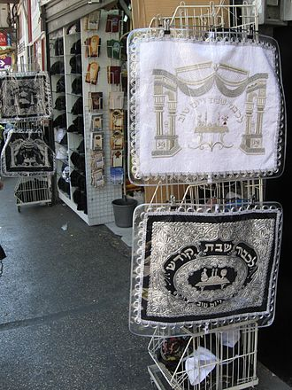 """Challah cover - Challah covers for sale outside a store in Jerusalem. The enscription on the top cover says """"To honor Shabbat and Yom Tov"""". The enscription on the bottom says """"To honor the holy Shabbat"""""""