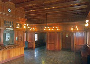 A room paneled in vertical wood planking, with a similar ceiling and floor. Antique lights and a ceiling fan hang from the ceiling.