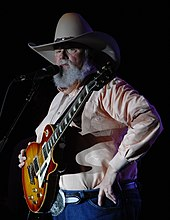A grey-haired man with a large beard wearing a cowboy hat, holding a guitar and talking into a microphone