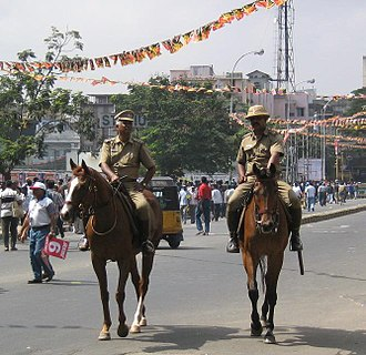 Khaki - Chennai City Mounted Police officers patrolling in their khaki colored uniform during a cricket match.