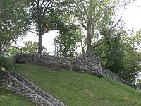 Photograph of a crumbling brick wall running up and then alongside a grassy hill which has trees and a lamppost at the top. Brick buildings are visible in the background to the left.