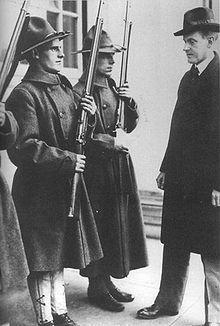 Photographie de Coolidge examinant plusieurs soldats en uniforme au garde-à-vous avec leurs fusils