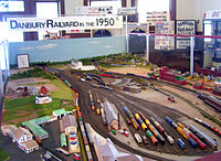 "A model train display with the station building at the left lower corner with various types of trains on the tracks next to the station and the railyard. A sign above it, on the upper left, reads ""Danbury Railyard in the 1950s"""