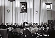 David Ben-Gurion proclaiming Israeli independence on May 14, 1948 below a portrait of Theodor Herzl