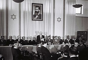 Israeli Declaration of Independence - David Ben-Gurion declaring independence beneath a large portrait of Theodor Herzl, founder of modern Zionism