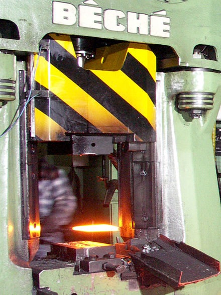 A red-hot metal workpiece is inserted into a forging press. Drop forging Gesenkschmieden.jpg