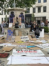 "The pedestal is seen with purple spraypaint graffiti ""BLM"" over two of the bronze plaques and black ""Black Lives Matter"" and stencilled raised fists on the plinth. Placards propped on the pedestal include ""Black Lives Matter"", ""Silence is Violence"", ""The UK is not innocent"" and ""In unity is strength"". Many more placards lie on the ground around the pedestal, with ""Black Lives Matter"",""Racism is a global pandemic"" and other slogans."