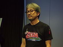 Homme d'origine asiatique debout portant un tee-shirt noir flanqué du logo du remaster du jeu The Wind Waker HD.