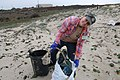 FWS biologist Jenny Marek with garbage and recyclables washed ashore (16444079431).jpg