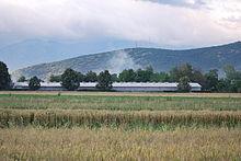Photographie de champs de céréales et d'une ferme industrielle dans le Polog