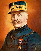 A gentleman with a handlebar-style moustache. He is wearing a peaked cap highly decorated with gold braiding. He wears a dark blue, high-collared jacket, with regularly spaced horizontal bands of dark braiding. On his left breast, he wears a medal attached to a red ribbon.