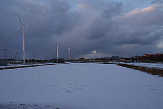 Clongriffin - Lake frozen over in Father Collins Park with distinctive wind turbines in the background