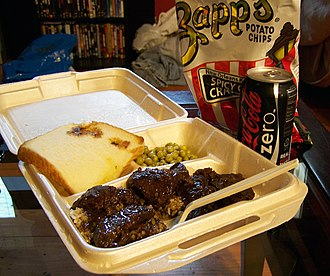 Smothering (food) - A plate lunch of smothered steak and gravy served over boiled white rice from Garys Grocery in Lafayette, Louisiana
