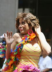 A white woman with brown hair, turning his head to the right, raising his right hand, with a yellow and pink dress, and a multi-colored boa around her neck.