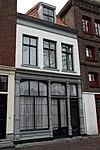 Huis onder schilddak met dakvenster. Gepleisterde lijstgevel
